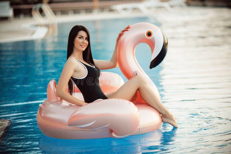 La mujer atractiva imponente está llevando el bikini negro que se sienta en piscina con agua azul en un colchón rosado del flamen fotografía de archivo