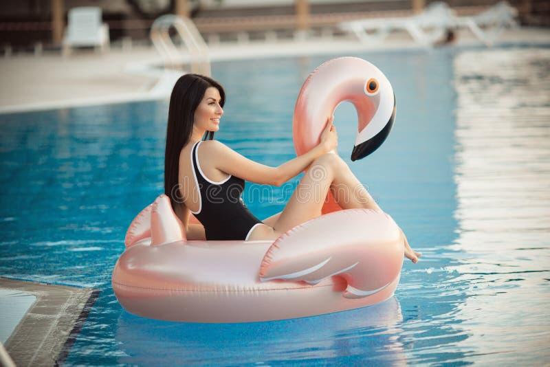 La mujer atractiva imponente está llevando el bikini negro que se sienta en piscina con agua azul en un colchón rosado del flamen foto de archivo libre de regalías