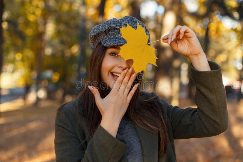 La mujer atractiva joven bonita feliz con una sonrisa en una capa y un sombrero de moda cubre su cara con su mano y un otoño amar imagen de archivo libre de regalías