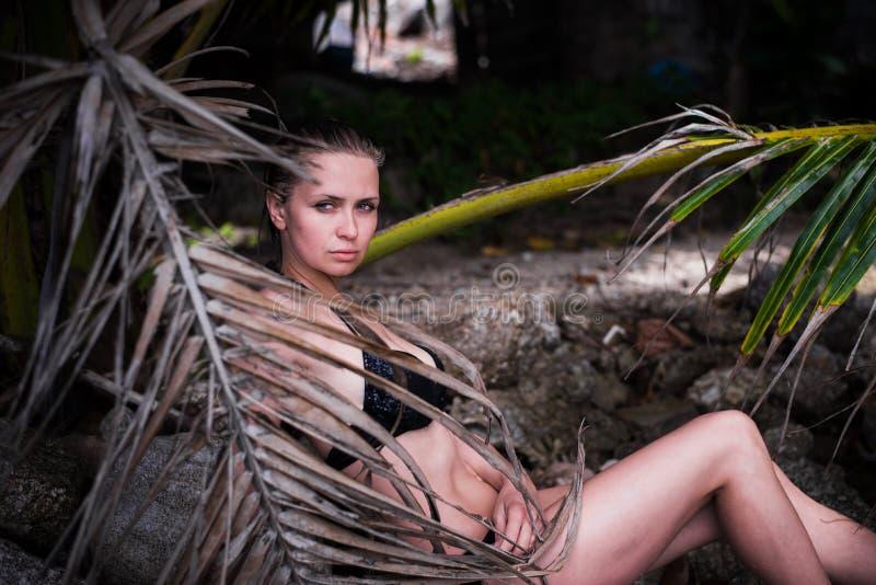La mujer atractiva joven con el cuerpo ideal en traje de baño negro está presentando en hojas de palma en selva imagen de archivo