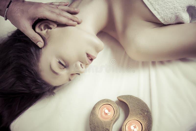 La mujer atractiva joven en balneario consigue un masaje facial fotos de archivo libres de regalías