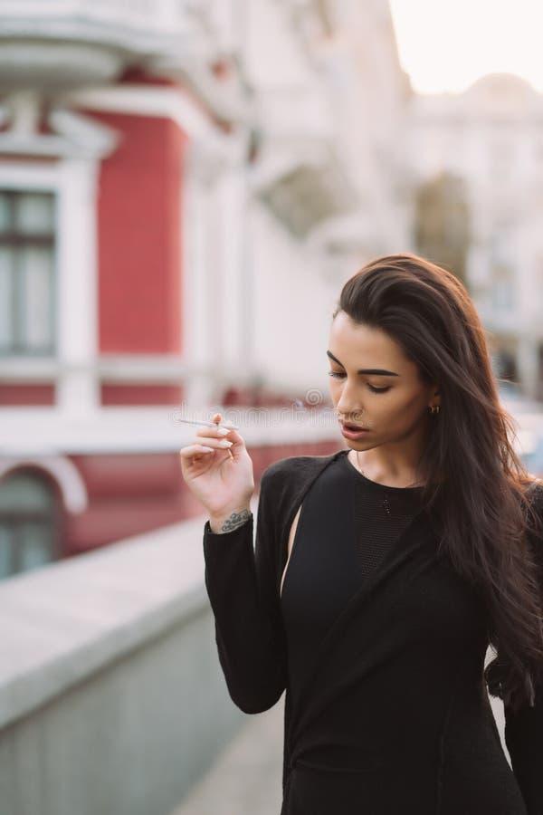 La mujer atractiva, joven en el cuerpo fuma en la calle foto de archivo
