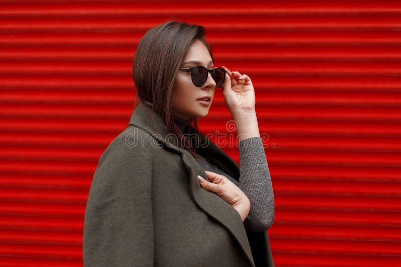 La mujer atractiva joven en una capa verde de la moda endereza las gafas de sol elegantes cerca de la puerta roja del metal foto de archivo libre de regalías