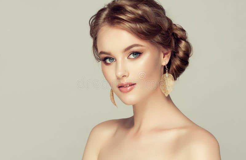 La mujer atractiva joven está demostrando el pelo rubio profundo recolectado en peinado exquisito imagen de archivo libre de regalías