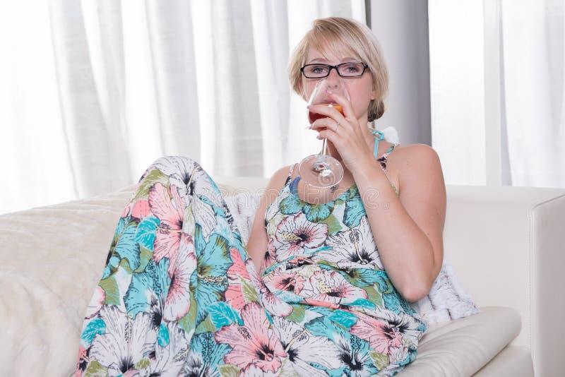 La mujer atractiva joven goza de un cóctel en el sofá foto de archivo