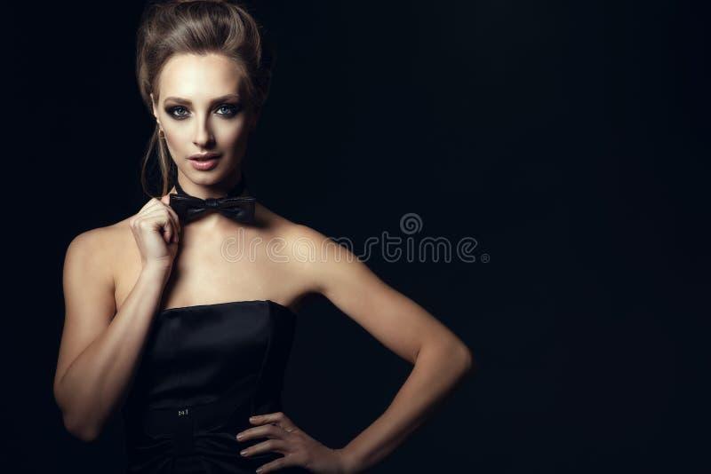 La mujer atractiva magnífica con hermoso componen y el pelo del updo que lleva la corbata de lazo conmovedora del vestido negro d fotos de archivo