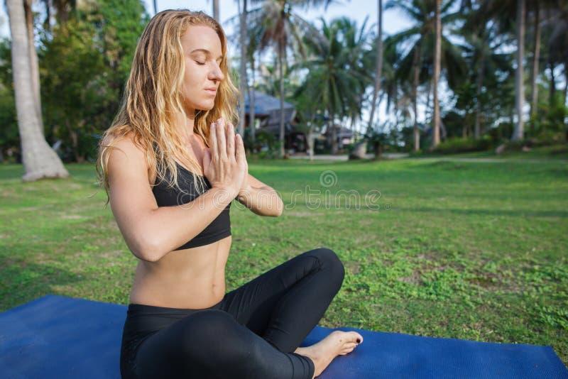 La mujer atractiva practica yoga en naturaleza imagenes de archivo