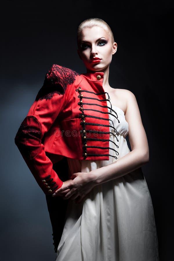 La mujer atractiva rubia en chaqueta roja y el blanco se visten fotografía de archivo libre de regalías