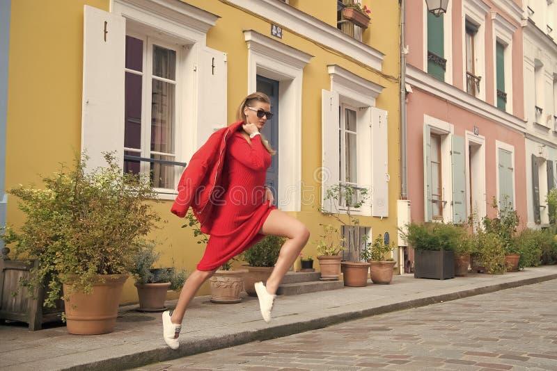 La mujer atractiva salta en la calle de París, Francia, vacaciones Mujer en gafas de sol, vestido rojo, zapatillas de deporte en  imagen de archivo