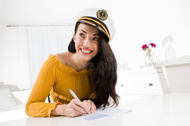 La mujer atractiva sonríe el sentarse y la tabla blanca y escritura con la pluma fotos de archivo