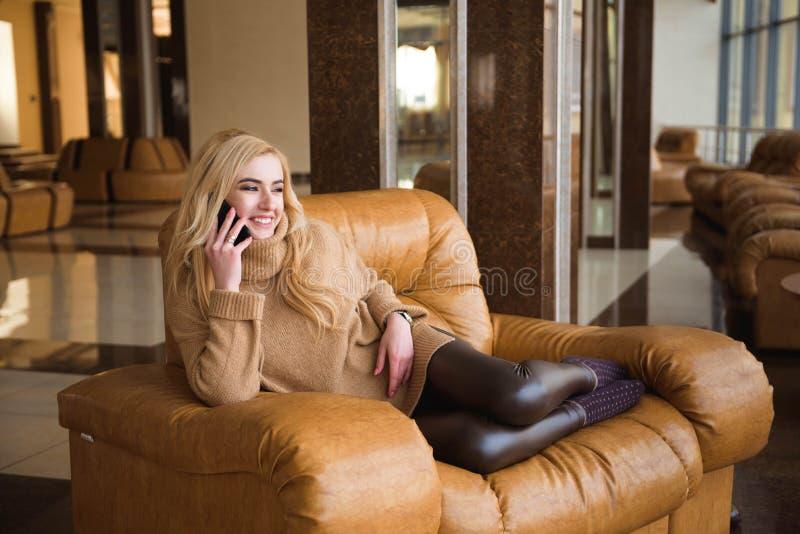 La mujer atractiva tiene un descanso para tomar café usando su teléfono móvil foto de archivo