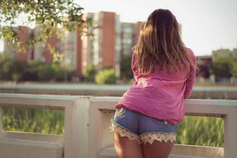 La mujer atractiva y atractiva que presenta con ella detrás, mirando en algo, dril de algodón casual atractivo que lleva pone en  foto de archivo libre de regalías
