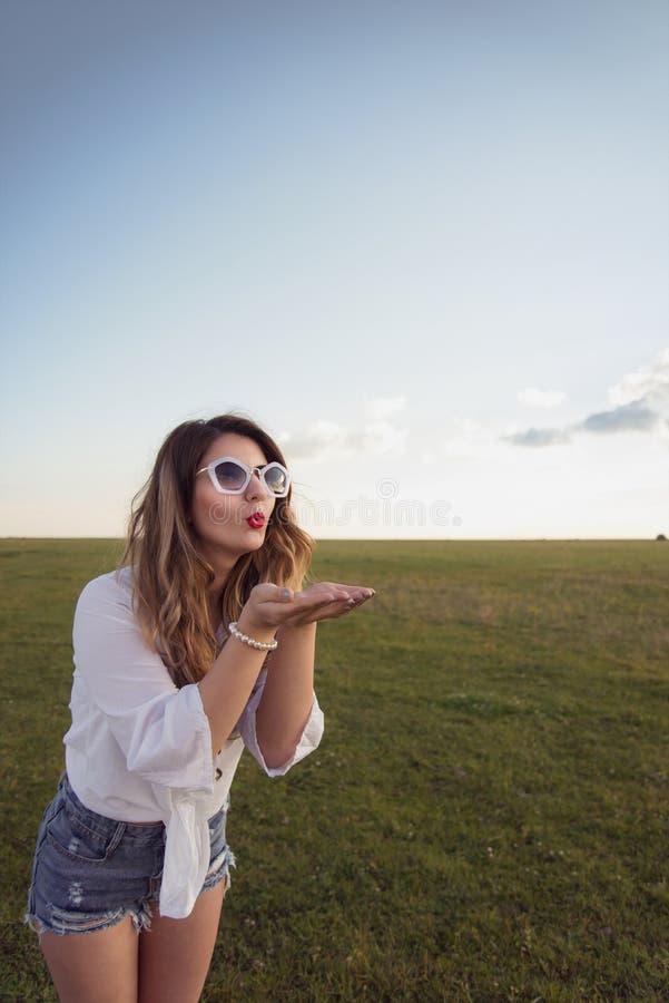 La mujer atractiva y hermosa que sopla de sus manos que llevan el dril de algodón atractivo pone en cortocircuito fotografía de archivo