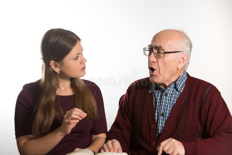 La mujer ayuda al hombre mayor imagen de archivo libre de regalías