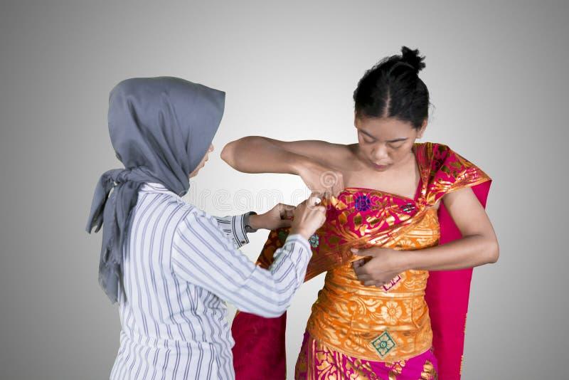 La mujer ayuda a un bailarín a llevar la ropa tradicional fotografía de archivo