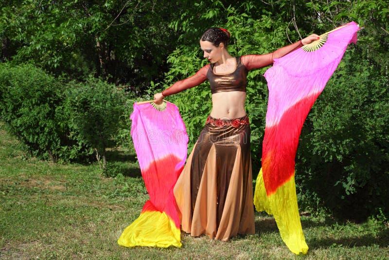 La mujer baila con los ventiladores del velo