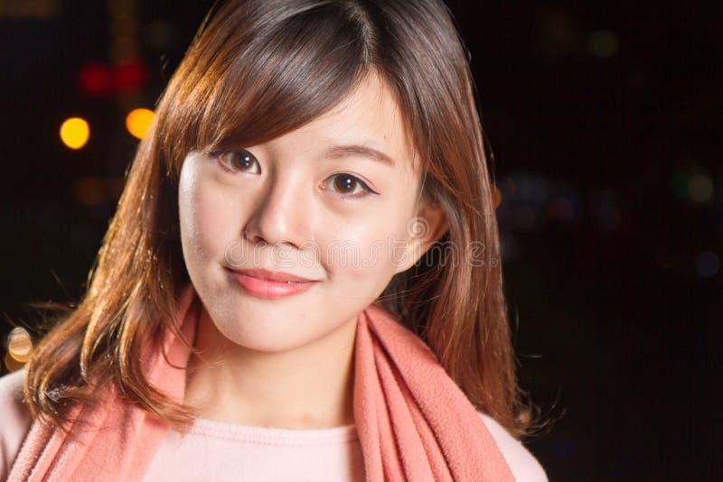 La mujer bastante asiática con la ciudad se enciende en fondo foto de archivo libre de regalías