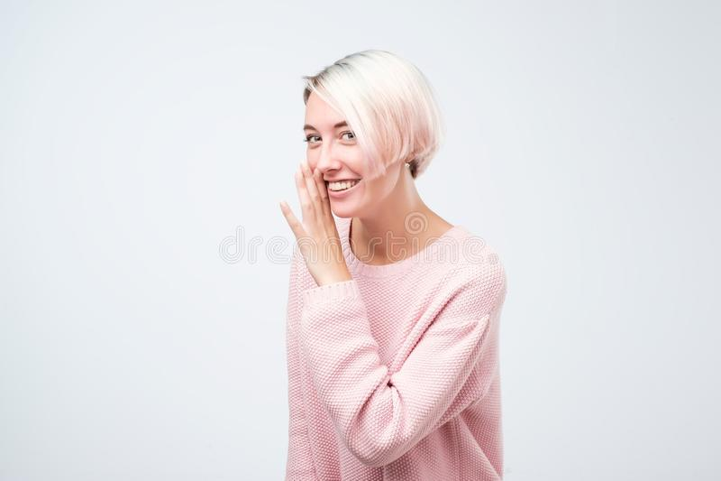 La mujer bastante hermosa misteriosa habladora con el pelo teñido vestido en suéter rosado está diciendo secreto fotos de archivo