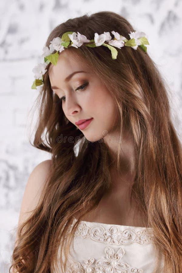 La mujer bastante joven en guirnalda con el pelo largo mira abajo imagen de archivo