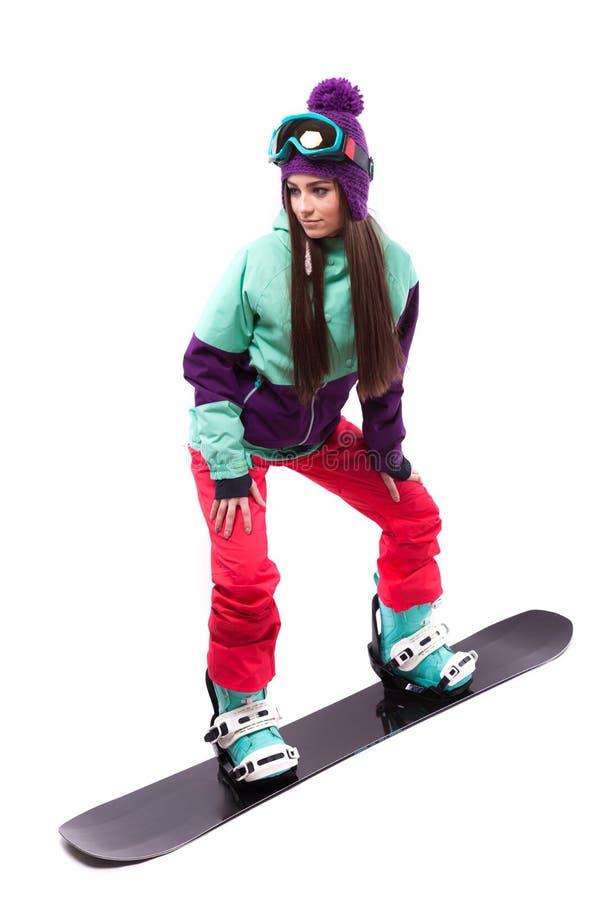 La mujer bastante joven en traje de esquí púrpura monta la snowboard negra fotos de archivo