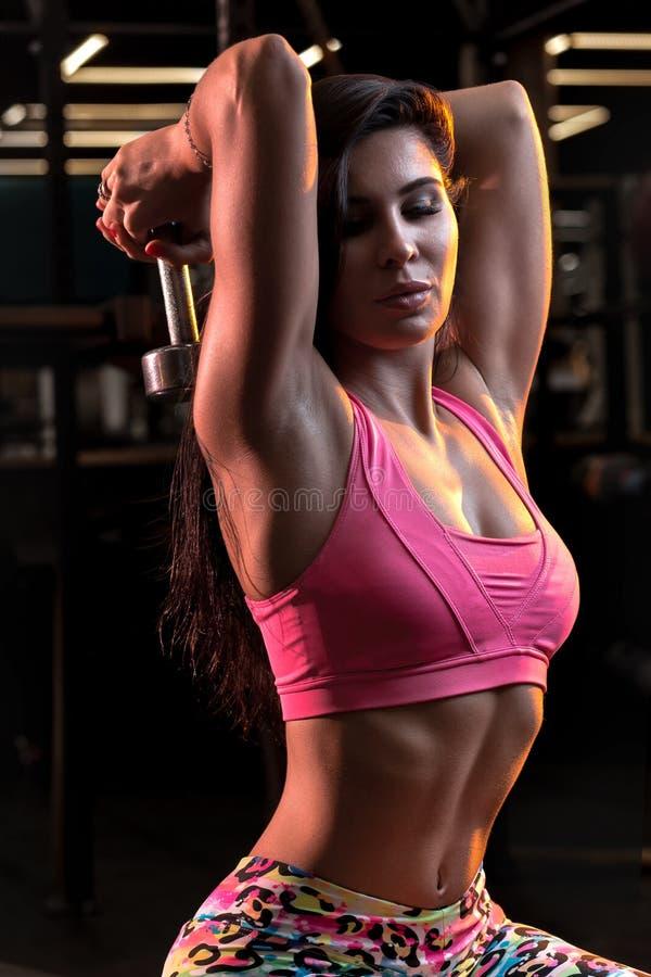La mujer bastante joven está haciendo rizos del tríceps con la pesa de gimnasia en el gimnasio foto de archivo