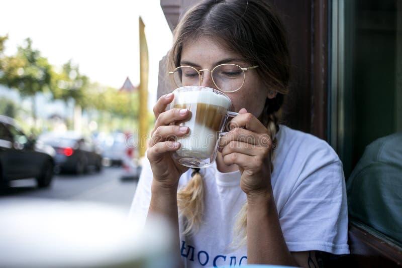 La mujer bastante joven linda bebe espuma de la leche del café foto de archivo libre de regalías