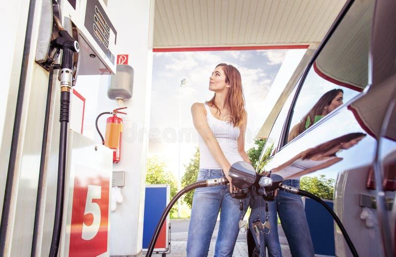 La mujer bastante joven reaprovisiona el coche de combustible fotos de archivo libres de regalías