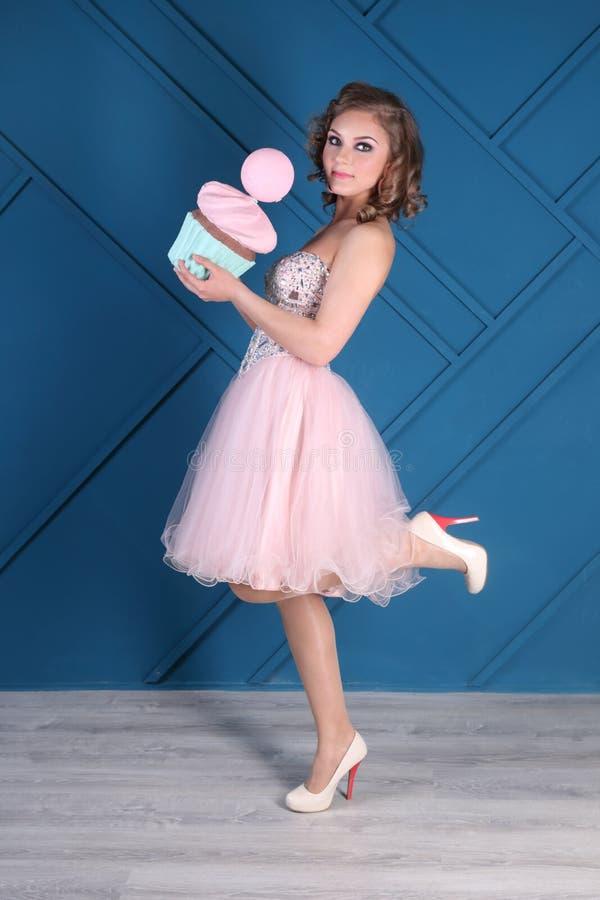 La mujer bastante rizada en vestido y talones rosados sostiene la magdalena imagen de archivo