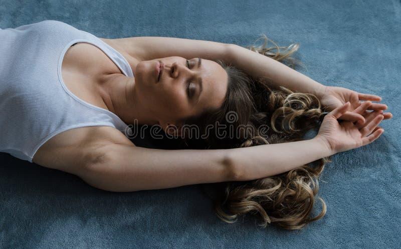 La mujer bastante rubia del pelo rizado de los jóvenes duerme en una cama azul imagen de archivo libre de regalías