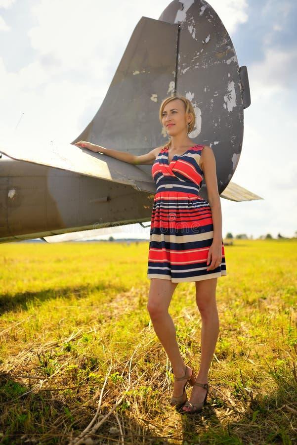 La mujer beautyful de la moda en vestido permanece cerca del viejo avión foto de archivo libre de regalías