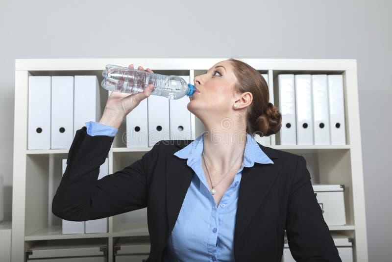La mujer bebe el agua en la oficina fotografía de archivo