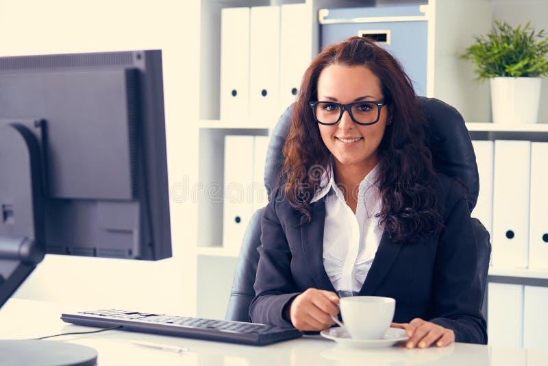 La mujer bebe el café en oficina fotos de archivo
