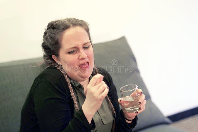 La mujer bebe una píldora del dolor imagen de archivo libre de regalías