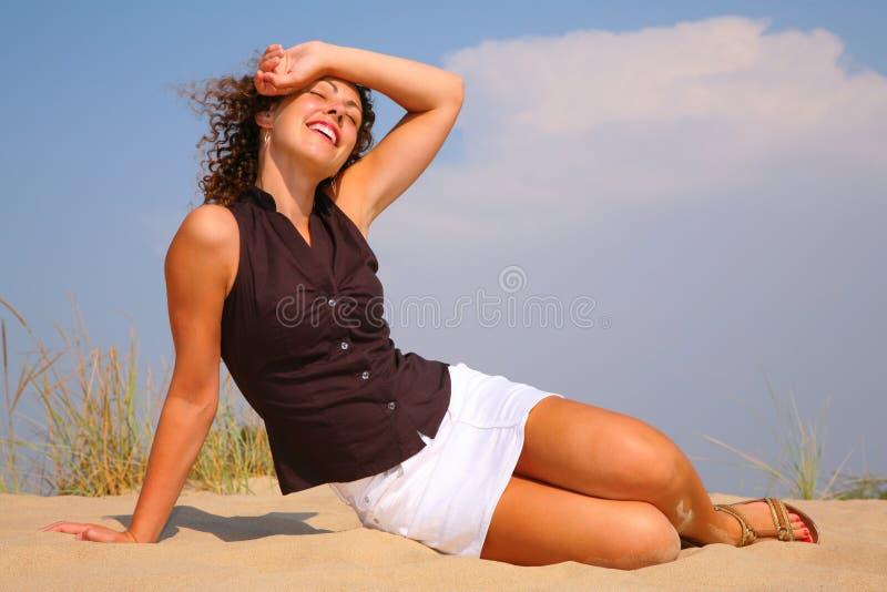 La mujer beuty joven se sienta en la arena fotografía de archivo libre de regalías