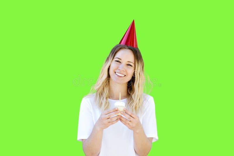 La mujer blanca sostiene una magdalena del cumpleaños mientras que sonríe en la pantalla verde fotografía de archivo