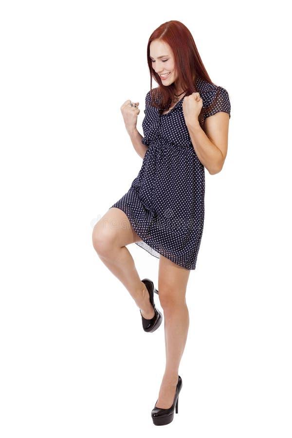 La mujer bonita con el pelo rojo hace una actitud de la victoria. foto de archivo libre de regalías