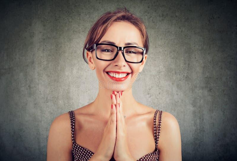 La mujer bonita con las palmas junta, tiene una expresión contenta de la cara, pidiendo a alguien un favor fotografía de archivo libre de regalías