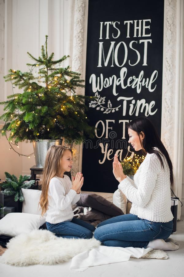 La mujer bonita elegante joven felicita a la hija en vestido en Navidad que juega con las manos en casa La niña la agradece fotografía de archivo