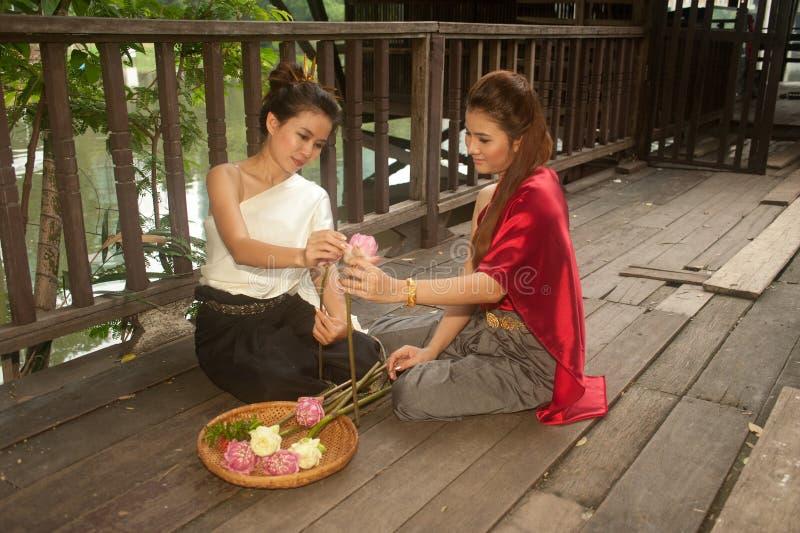La mujer bonita en estilo tailandés viste en la presentación de las flores artificiales. fotografía de archivo libre de regalías