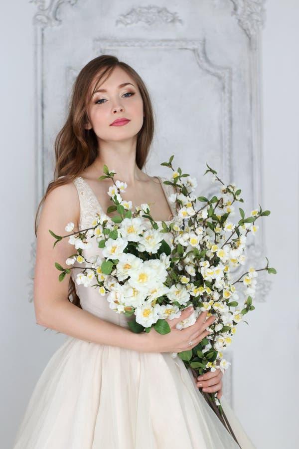 La mujer bonita en vestido largo sostiene las flores blancas imágenes de archivo libres de regalías