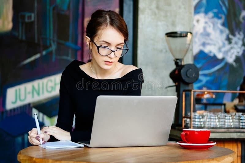 La mujer bonita en vidrios trabaja en un ordenador portátil, aplicaciones un smartphone, freelancer, un ordenador, analista finan fotos de archivo libres de regalías