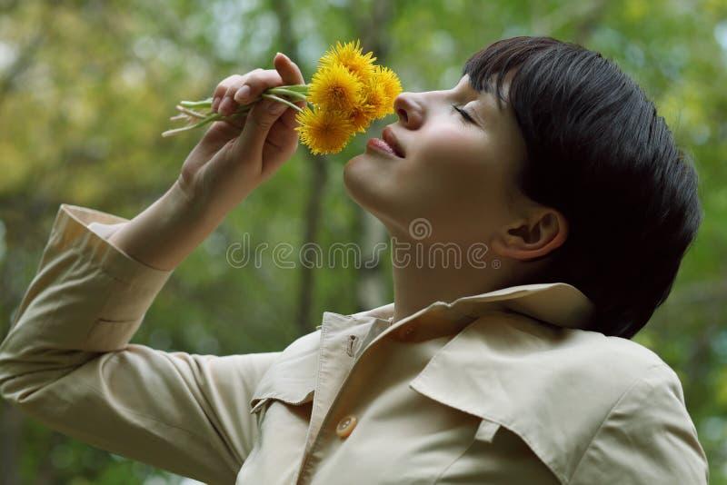 La mujer bonita está oliendo las flores en el parque foto de archivo