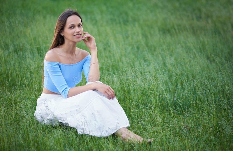 La mujer bonita feliz se está sentando en una hierba fotografía de archivo libre de regalías