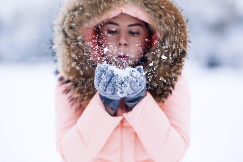 La mujer bonita feliz sonriente en chaqueta caliente del invierno al aire libre goza del viaje del invierno, de los guantes weare imagen de archivo libre de regalías