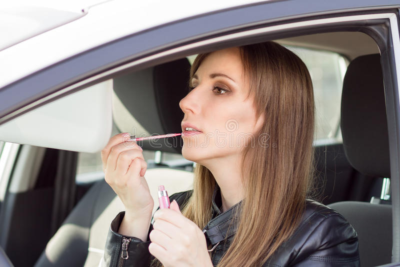 La mujer bonita joven aplica maquillaje en coche fotografía de archivo libre de regalías