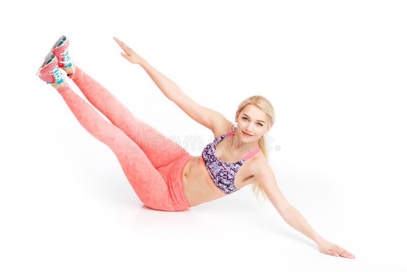 La mujer bonita joven apta que hace el ABS ejercita en el piso Concepto de la salud fotografía de archivo