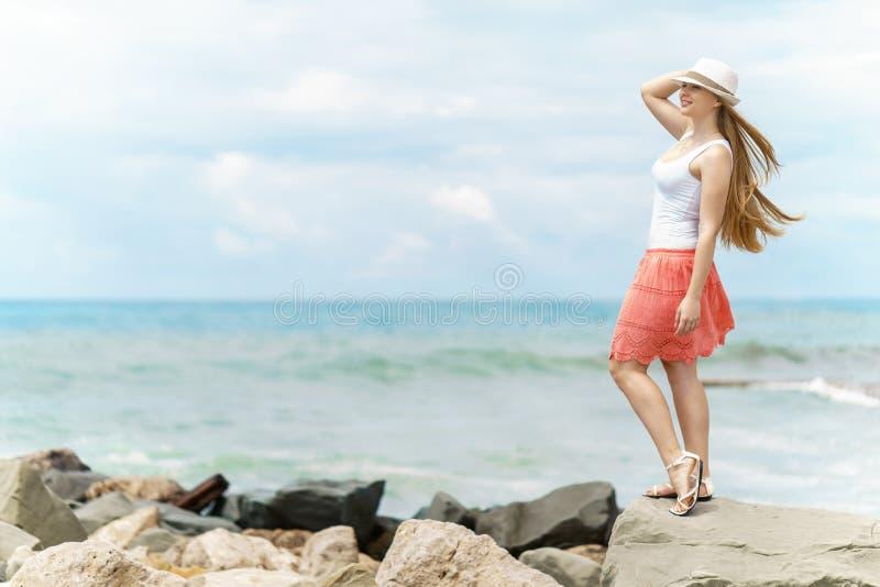 La mujer bonita joven con el sombrero blanco y la falda roja staing en piedra en la costa debajo del cielo gris con el fondo fuer imagenes de archivo