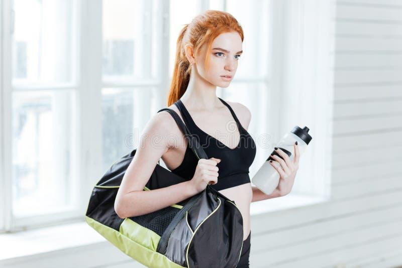 La mujer bonita joven de la aptitud con deportes empaqueta y botella de agua fotos de archivo