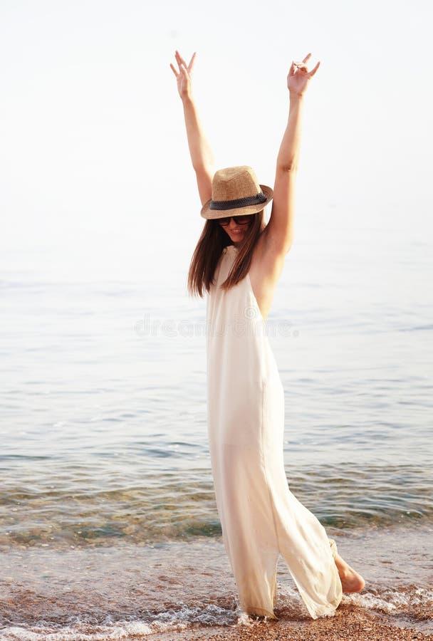 La mujer bonita joven disfruta de vacaciones de verano toma un resto en una playa del mar imagen de archivo