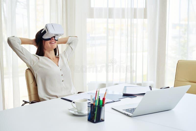 La mujer bonita joven es relajante en realidad virtual imagenes de archivo